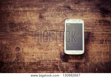 Broken smart phone on wooden background, copy space for text. Cellphone service