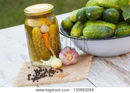 Ripe cucumbers in metal bowl spices for pickling and jar marinated cucumbers on old white table in garden on sunny day