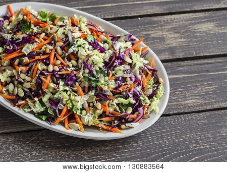 Fresh Cole slaw with pumpkin flax sesame seeds and pine nuts - delicious healthy vegetarian food. On a dark rustic wooden background
