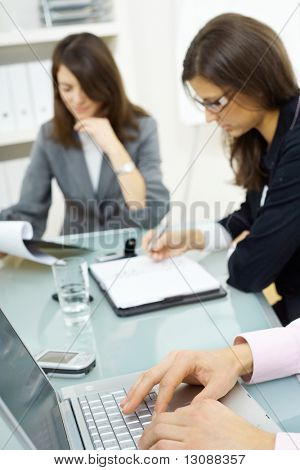 Young businesspeople sitting around table. Two businesswomen looking at notes. Selective focus placed on hands typing on laptop computer.