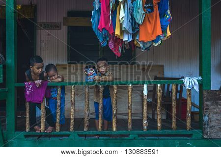 Mabul Island Sabah Malaysia - May 1 2016 : A shot of local kids at a colorful balcony. The shot was taken at Mabul Island Sabah Malaysia.