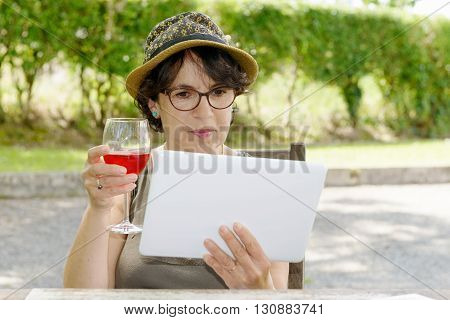 a charming woman with a tablet and glasse of wine in her garden