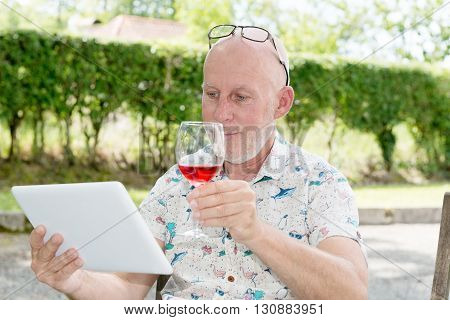 man with a tablet and glass of red wine in garden