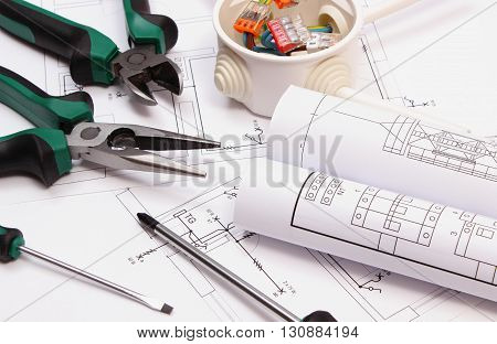 Work tools rolls of diagrams and cable connections in electrical box lying on construction drawing work tool for engineer jobs concept of building house