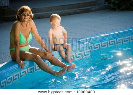 Grandmother and two years old granson enjoy water and sunshine on the poolside. Natural light, summer.
