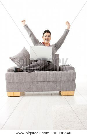 Happy businesswoman sitting on sofa with laptop computer. Celebrating business succes with hands raised, smiling.