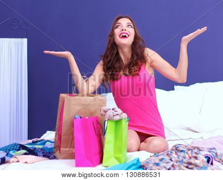 Pretty young woman sitting a bed with shopping bags after successful shopping.