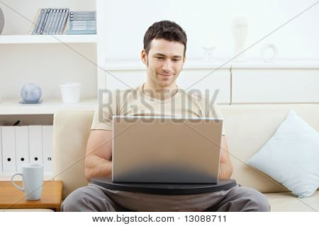 Happy casual man using laptop computer at home, sitting on couch, simling.