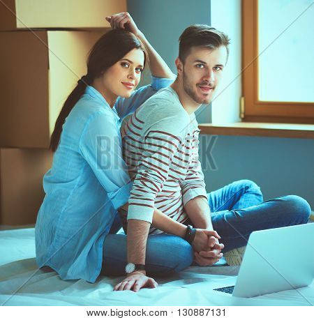 Young couple  sitting on the floor of their new apartment.
