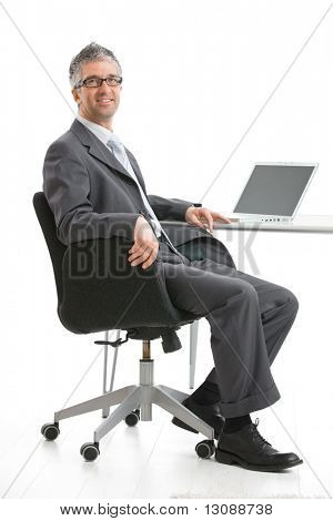 Businessman sitting at desk and working with laptop computer. Looking at camera, smiling. Isolated on white, copy space on screen.
