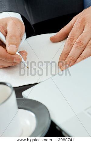 Hands of businessman drawing graph on paper napkin on coffee table.