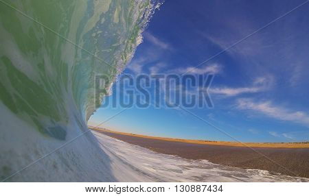 Powerful wave crashing on empty beach under sunny skies in California: Point of view perspective.