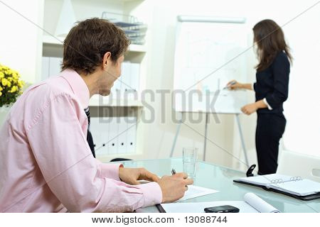 Young businessman sitting at desk, writing notes. Businesswoman standing in background, drawing chart on whiteboard. Selective focus on man.