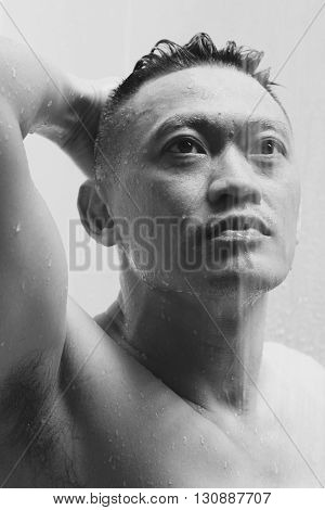 An Asian man showering with his eyes gazing at something