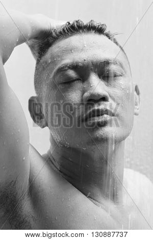An Asian man showering with his eyes closed