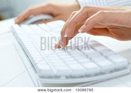 Closeup imagen de mano mujer escribiendo en el teclado de la computadora de escritorio.