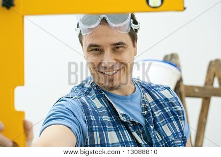 Worker measuring with square level tool, smiling. Isolated on white background.