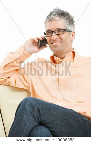 Casual man wearing jeans and orange shirt sitting on couch, talking on mobile phone. Isolated on white.