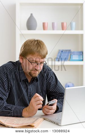 Man writing SMS on smart phone at home, sitting at table with laptop and newspaper on it.