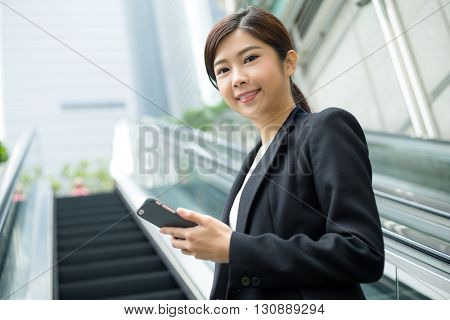 Businesswoman hold with cellphone and standing at escalator