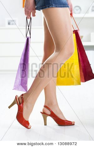 Long female legs in stockings. Hands holding colorful shopping bags.