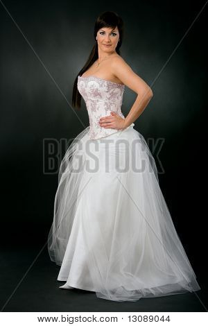Bride wearing romantic white wedding dress, posing with her hands on hip, looking at camera, smiling.