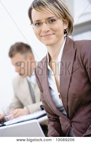 Portrait of young businesswoman in office. Businessman working in the background.