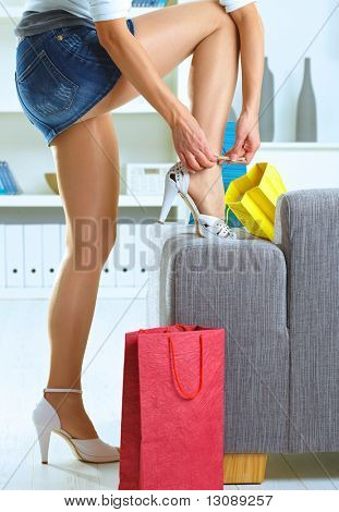 Long female legs in stockings. Woman taking off shoes after shopping at home.