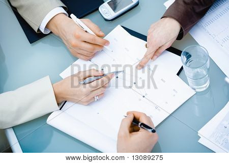 Close-up of hands of teamworking businesspeople on meeting at office.