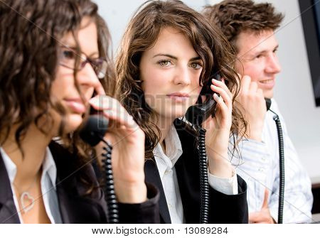 Young customer service operator team working at office, holding phone, calling, giving helpdesk support.