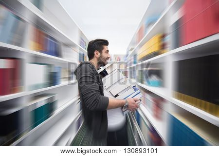 Student in library holding lot of books  Hard worker and persistence concept in education with motion and zoom blur effect