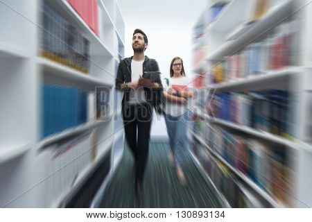 students couple in library  looking for books   and walking with motion blur effect
