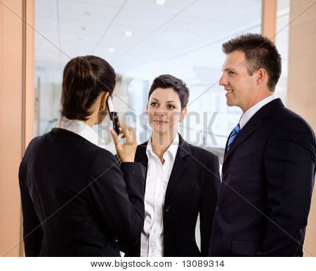 Business team standing in office hallway, businesswoman talking on mobile phone.