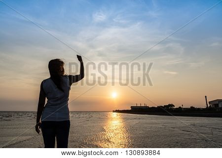 woman with arm raised up feeling success and strong on sunset background