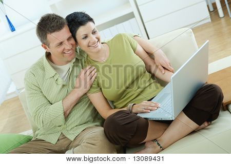 Young couple sitting on couch at home and using laptop computer.