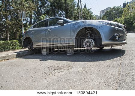 Haifa, Israel, April 4, 2016 : Car on blocks with four stolen wheels in the street