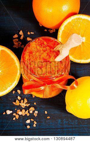 Homemade sugar scrub with Orange on a wooden background