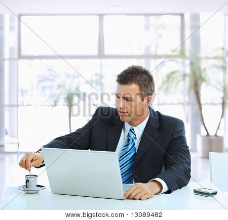 Businessman sitting at table in office lobby, stirring coffee and using laptop computer.