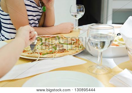 Somebody cutting pizza using pizza knife. Glasses with water on the table.