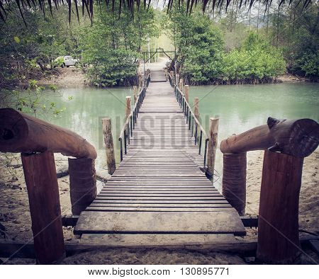 Old wooden bridge across the river. LOMO effect