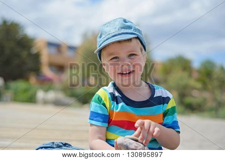 Portrait of happy little boy in multicolored t-shirt sitting on sandy beach
