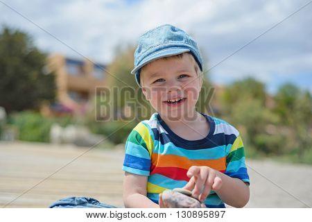 Portrait of happy little boy in multicolored t-shirt sitting on sandy beach
