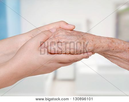 Senior lady and young women holding hands in hospital