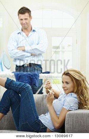 Relaxed young woman sitting on couch filing her nails, man watching with hands crossed behind ironing board.