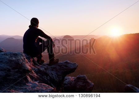 Tired Adult Hiker In Black Trousers, Jacket And Dark Cap Sit On Cliff Edge And Looking To Colorful M