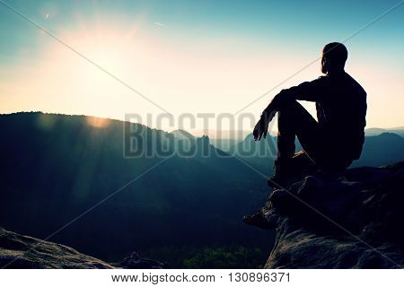 Tourist Take A Rest. Handsome Young Man Sitting On The Rock And Enjoying View Into Misty Rocky Mount