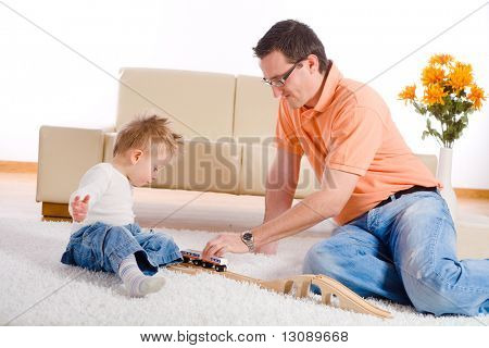 Father and baby boy playing together at home, sitting on floor.