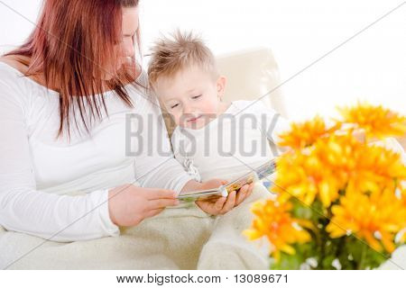 Happy family sitting on sofa at home mother reading for baby boy from story book.