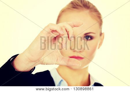 Young businesswoman showing copy space or something between fingers