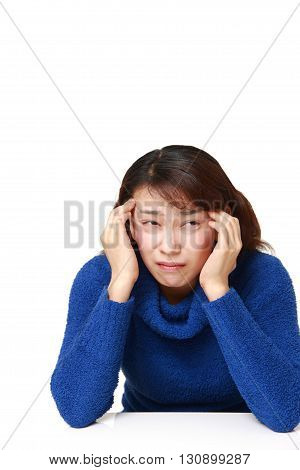 portrait of Asian businesswoman suffers from headache on white background